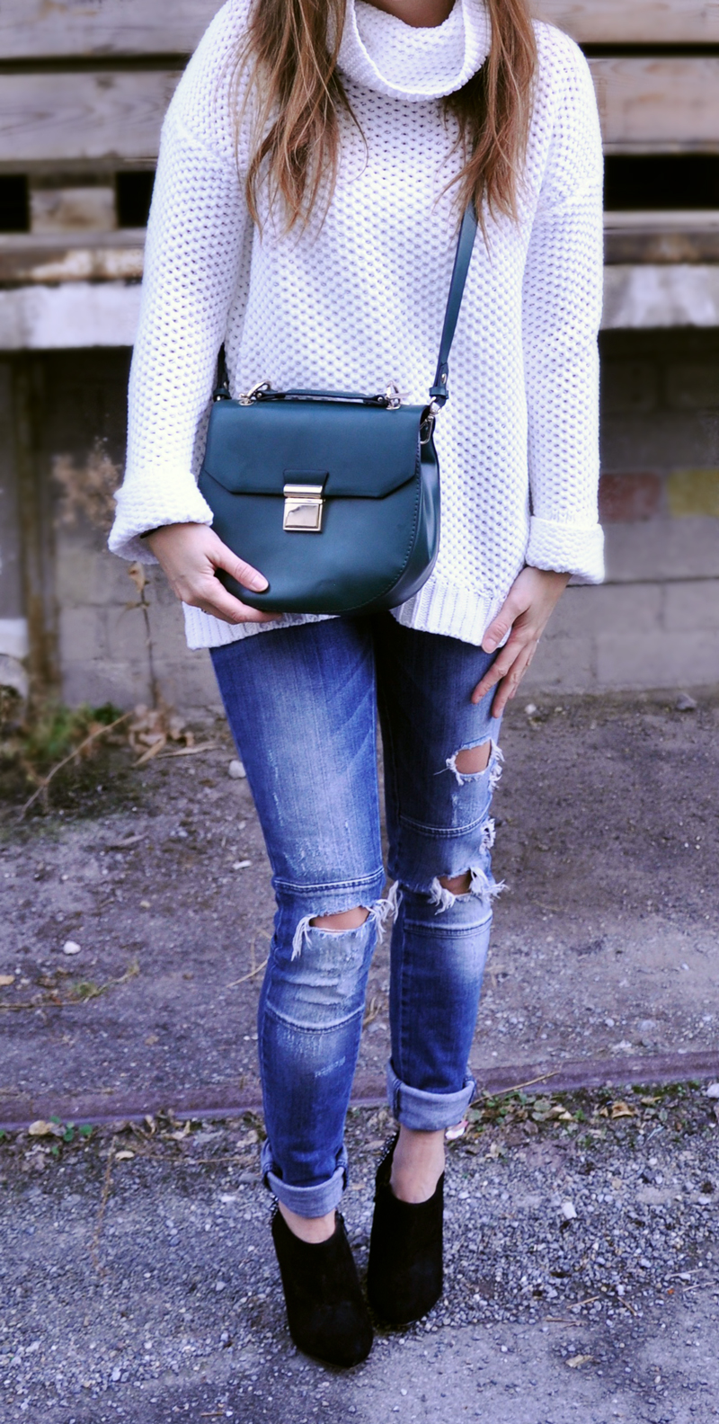 A white oversize turtleneck from Forever 21 with destroyed jeans from Only. Then black high-heels with rivets from Aldo and a green bag from Zara.