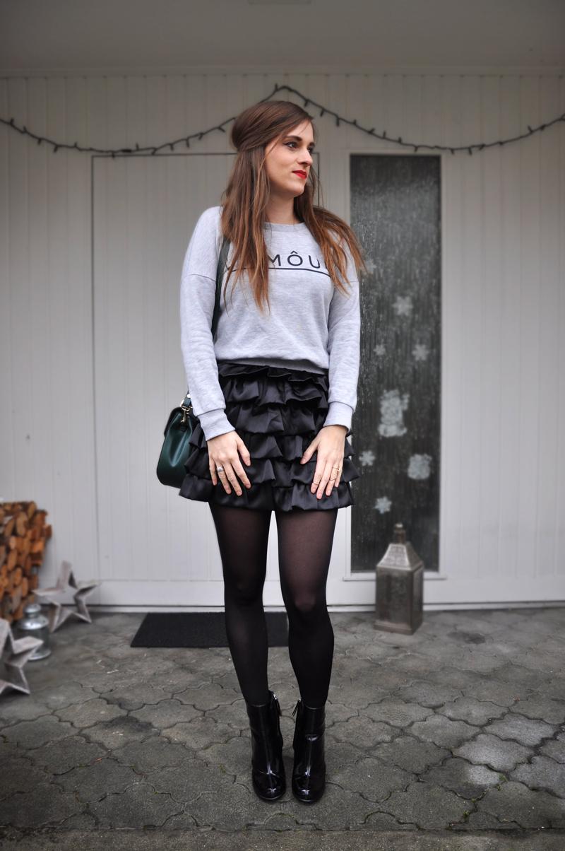 schwarzer Rüschenrock von Mango mit kurzem Pullover von H&M. Dazu Lackstiefel von H&M sowie eine grüne Tasche von Zara. Die Strümpfe sind von Wolford.