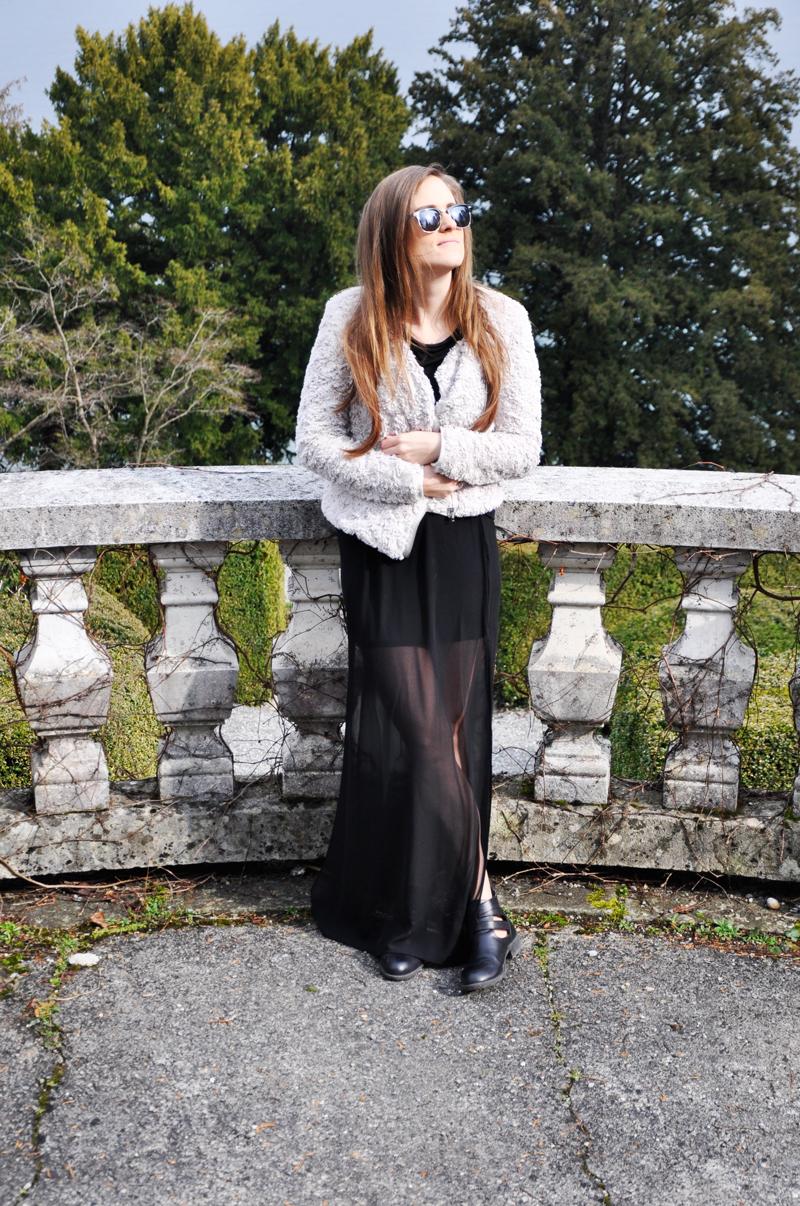 Schwarzer bodenlanger Rock von H&M mit einer grauen Felljacke, schwarze Stiefel von New Yorker und ein schwarzes T-Shirt von River Island.