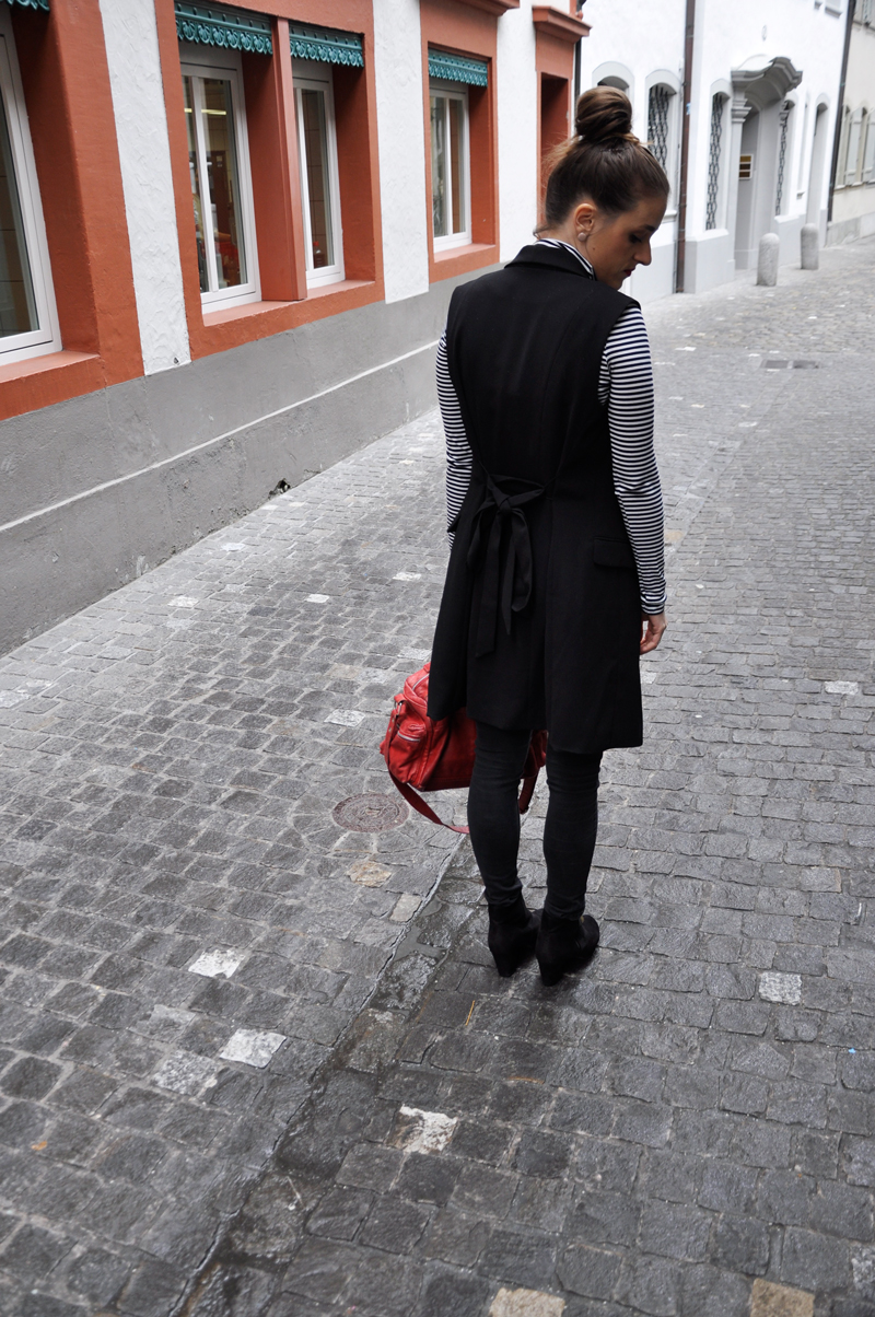 Dark skinny pants from ONLY, a turtleneck from H&M and a long black Vest from H&M. The shoes are from Tokyo and a red bag also from H&M.