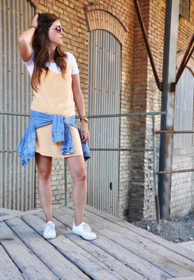 Kleid mit Spaghettiträgern von Mango, darunter ein weisses T-Shirt von H&M mit einer Jeansjacke von American Eagle. Eine Sonnenbrille in Rundum-Form von H&M mit weissen Sneakers.