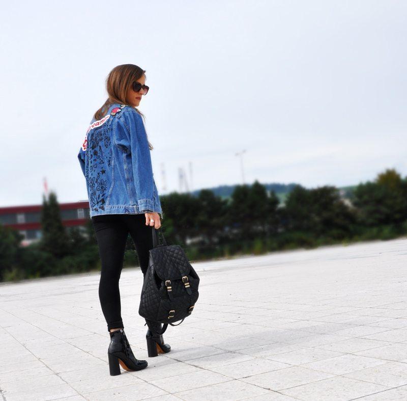 Flashback: Jeansjacke mit Aufnähern. Eine Jeansjacke mit Aufnähern von ASOS, dazu schwarze Hosen von Vero Moda und ein schlichtes Top von H&M. Der Rucksack war ein Geschenk und die Schuhe sind von H&M. Die Accessoires sind ebenfalls von H&M und ASOS.