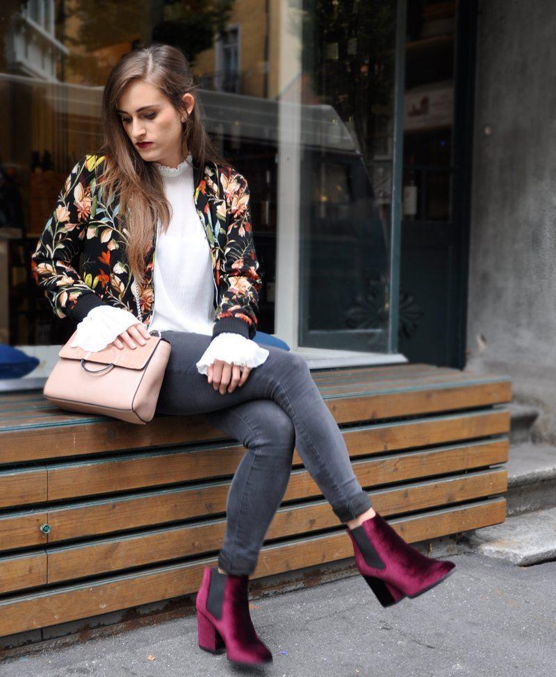 Skinny Jeans mit einer Rüschen-Bluse dazu eine Bomberjacke mit Blumenmuster von Zara und rote Samtschuhe von Zalando.