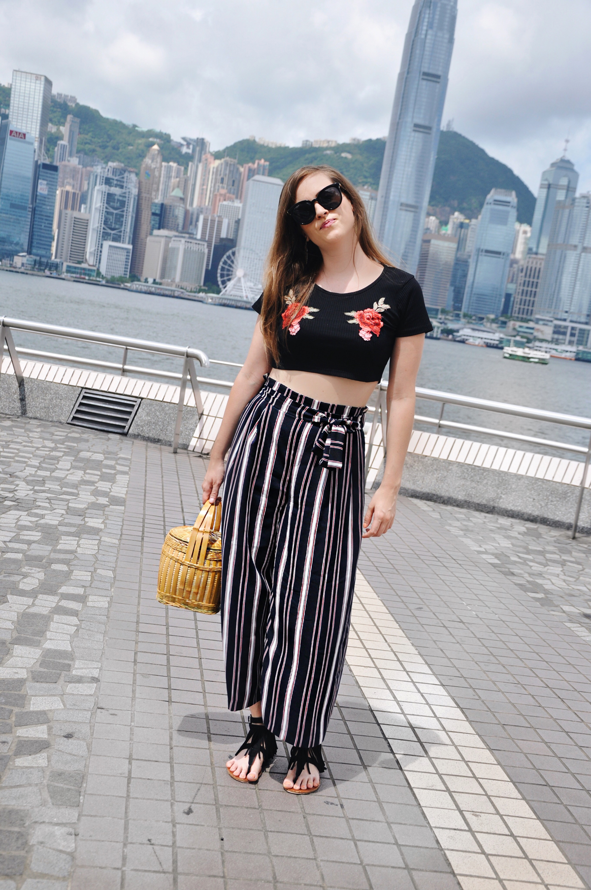 Fashionblogger, Andrea Steiner from Strawberries 'n' Champagne wear in Hong Kong a cropped top with flower prints from romwe.com with striped pants from Zara. The basket is handmade from a street market in Guizhou and the sunglasses from Muji in Shanghai and the shoes from Forever 21.