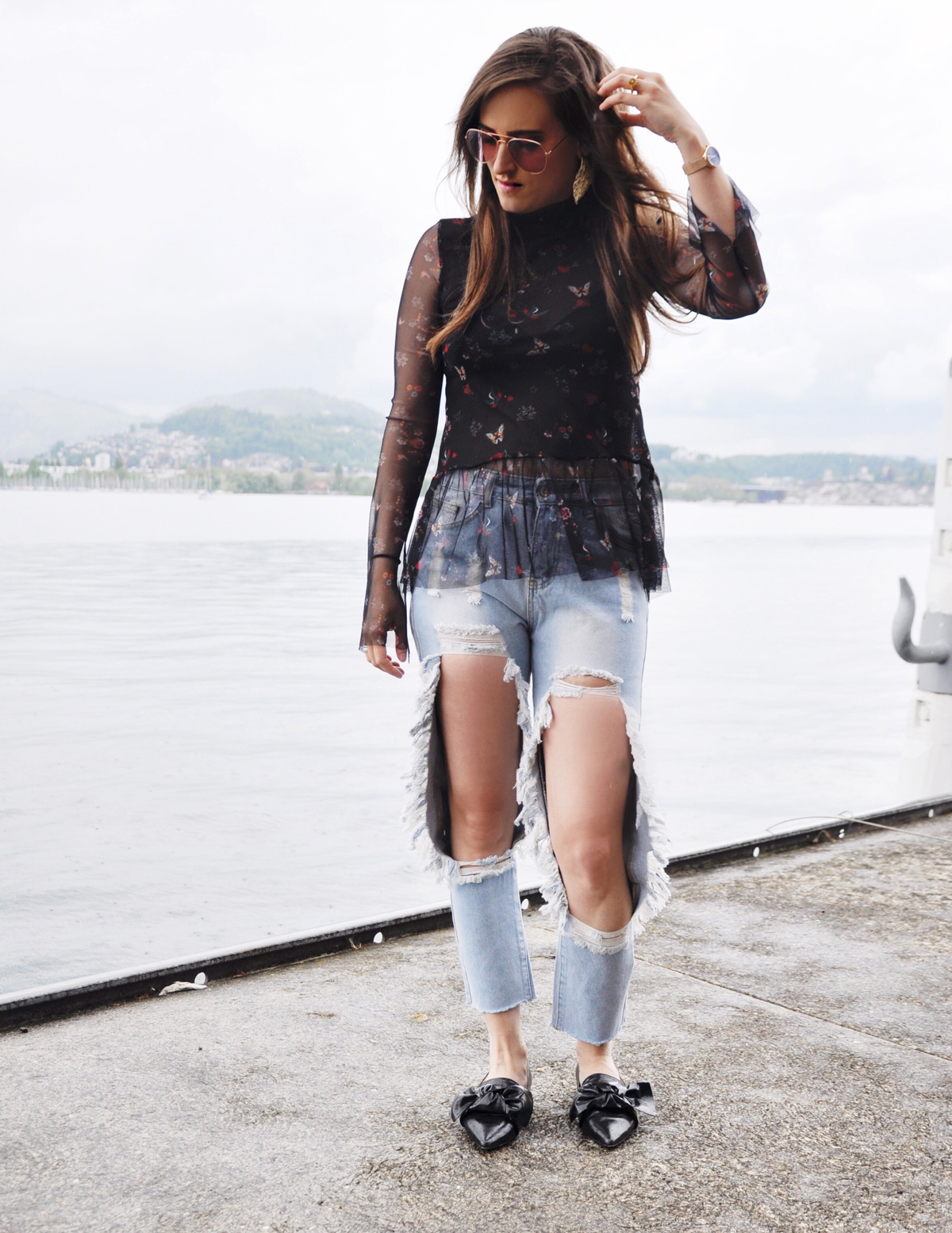 Fashionblogger, Andrea Steiner from Strawberries 'n' Champagne is wearing ripped jeans from shein.com combined with a tulle shirt from Stradivarius. The shoes are from Zara and the sunglasses from flea market.