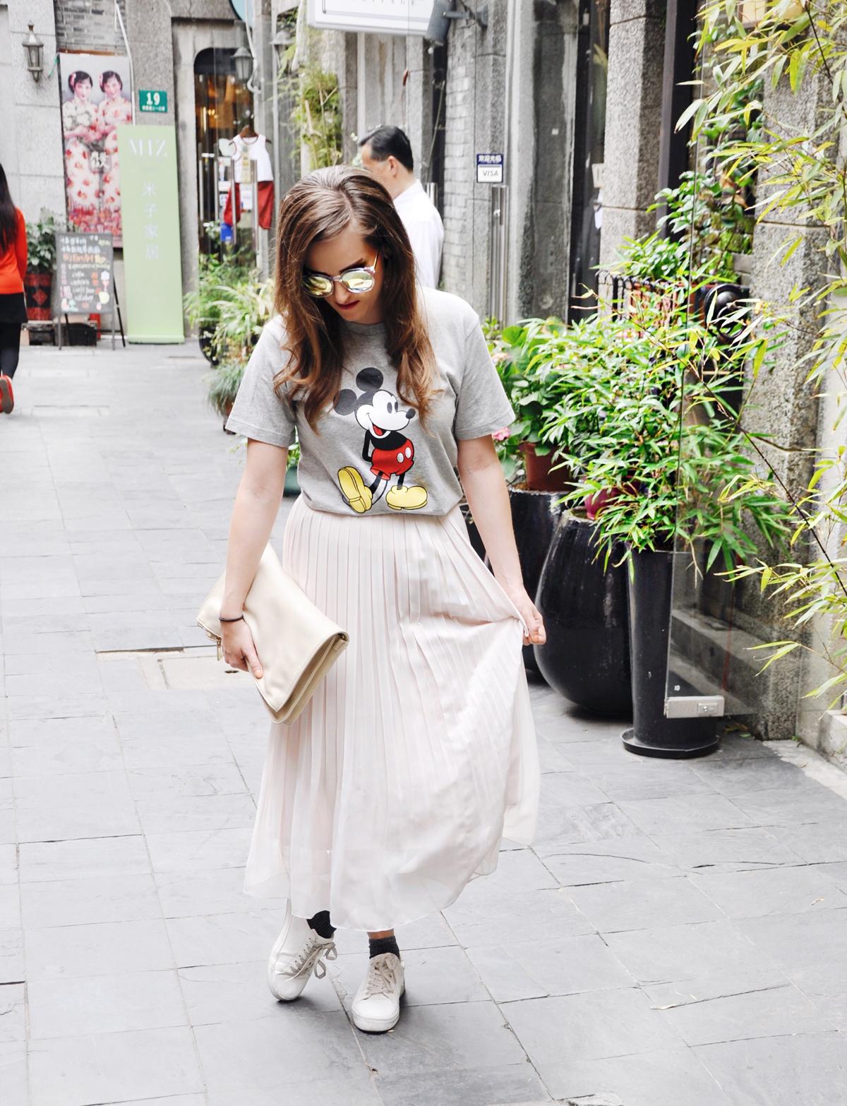 Fashionblogger Andrea Steiner von Strawberries 'n' Champagne trägt in Shanghai einen langen Faltenrock von Uniqlo, dazu ein Mickey Mouse Shirt auch von Uniqlo, mit einer Sonnenbrille von Muji und einer Clutch von H&M.
