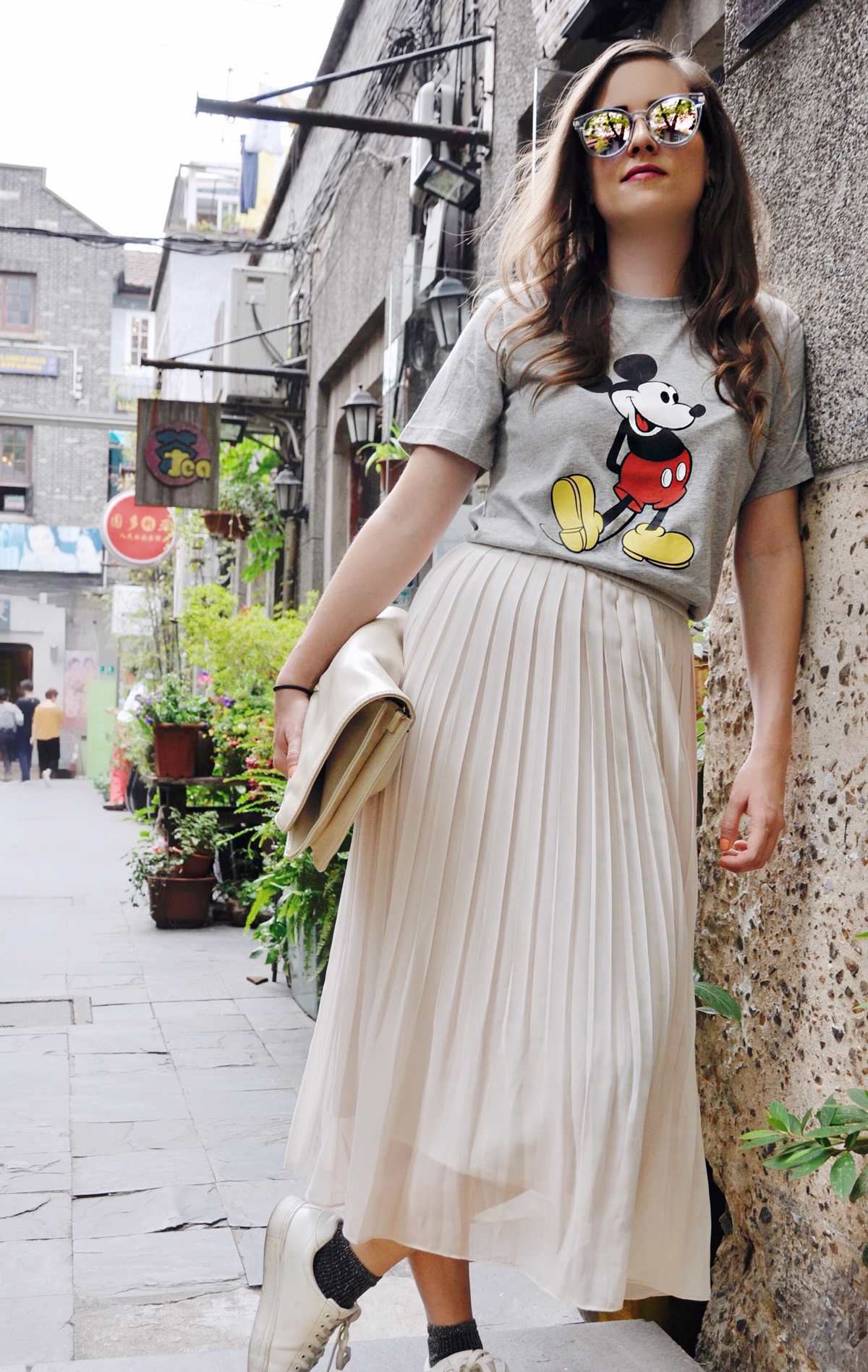 Fashionblogger Andrea Steiner from Strawberries 'n' Champagne wearing in Shanghai a long skirt from Uniqlo with a Mickey Mouse shirt also from Uniqlo. The sunglasses is from Muji and the clutch from H&M.