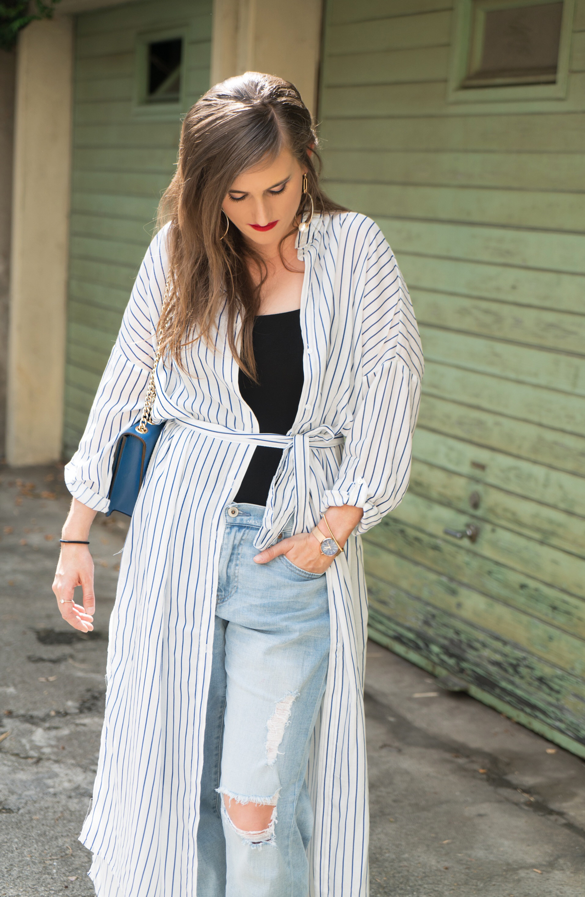Fashionblogger, Andrea Steiner from Strawberries 'n' Champagne is wearing a long striped blouse from Zara with ripped jeans from Uniqlo and a black basic top from H&M. A Moschino bag and shoes from Hong Kong. Make up is Yves Saint Lauren and Mac Cosmetics.