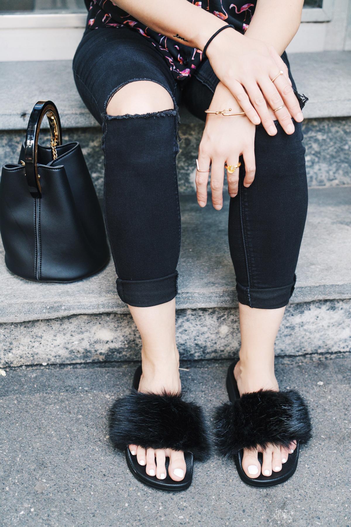 Andrea Steiner Fashionblogger von Strawberries 'n' Champagne trägt eine schwarze Bluse mit Flamingos von Topshop, dazu schwarze Jeans von River Island. Hut ist von H&M und die Schuhe ebenfalls von Topshop. Ohrringe und Tasche sind von Hongkong und das Armband von Skagen Denmark.