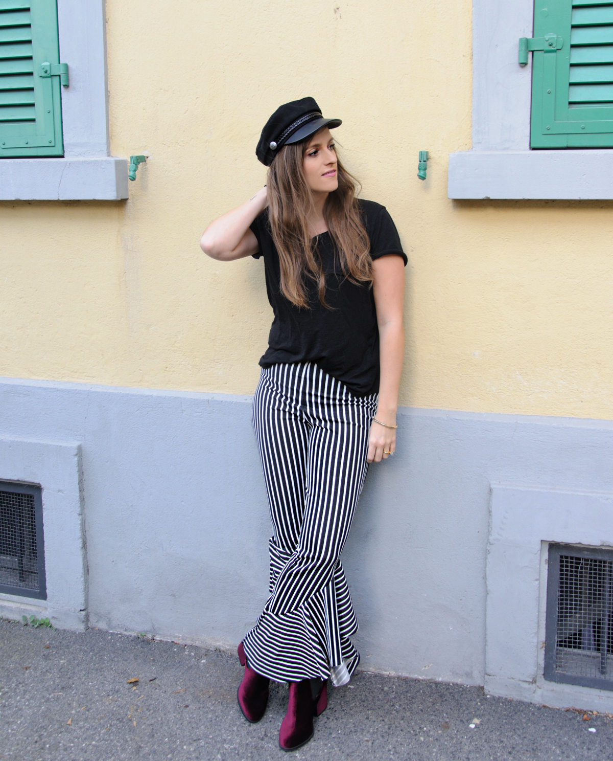 Andrea Steiner, Fashionblogger from Strawberries 'n' Champagne is wearing for Fall a black boy hat with ruffle pants, a basic shirt and a long blue coat.