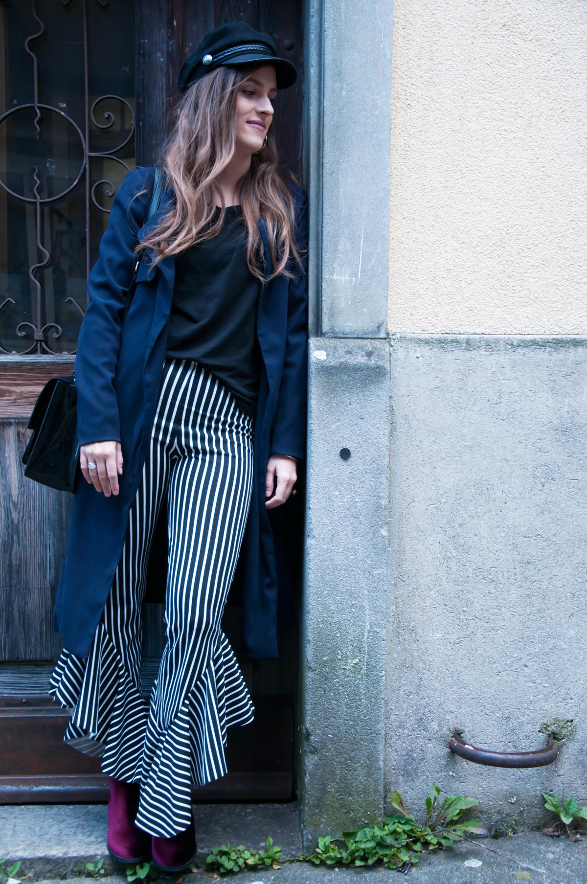 Andrea Steiner, Mobebloggerin von Strawberries 'n' Champagne trägt passend zum Herbst eine Schiffermütze, dazu gestreifte Rüschenhosen, ein Shirt und ein langer Mantel.