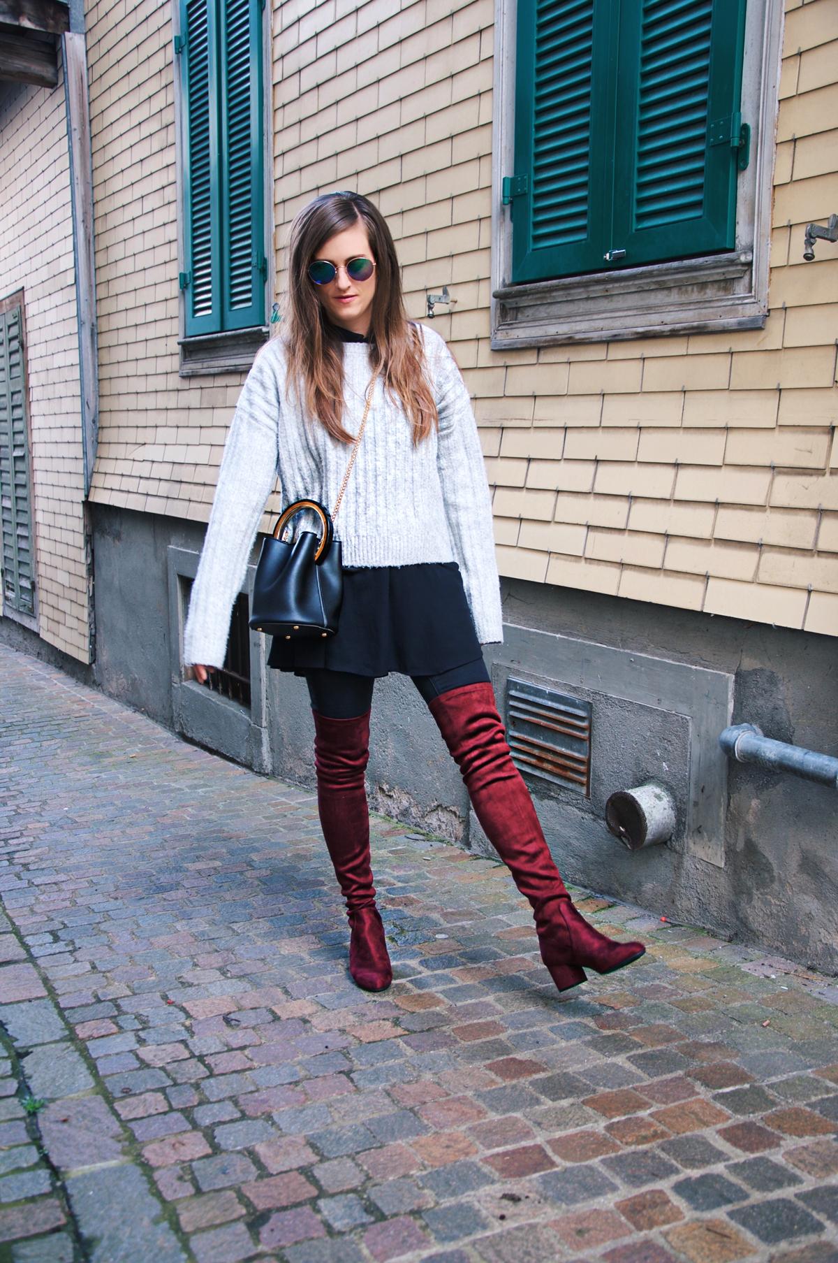 Andrea Steiner Modebloggerin von Strawberries 'n' Champagne trägt rote Overknees von Steve Madden, dazu schwarze Hosen von Topshop und ein Pullover von H&M. Die Tasche ist aus einer Boutique aus Hong Kong.