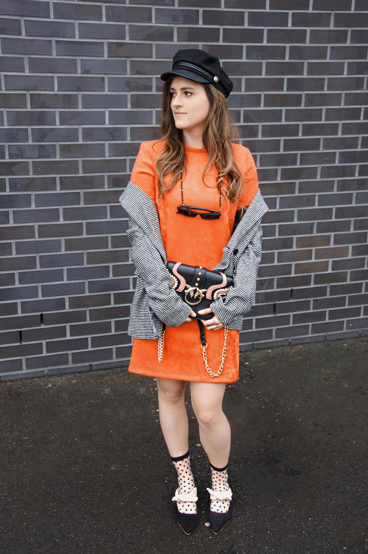 Andrea Steiner Mode Bloggerin von Strawberries 'n' Champagne aus der Schweiz trägt ein oranges Kleid mit einem Blazer.