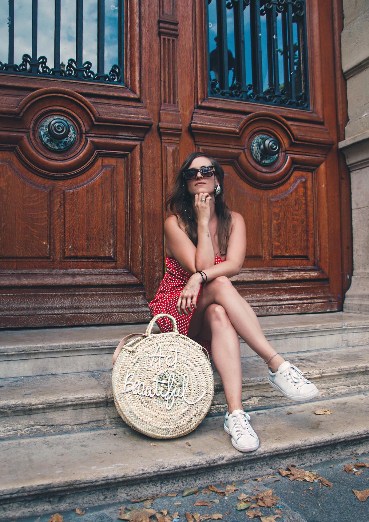 Ein rotes Kleid mit weissen Punkten, weisse Sneakers und eine Strohtasche für die Fashion Show in Paris.