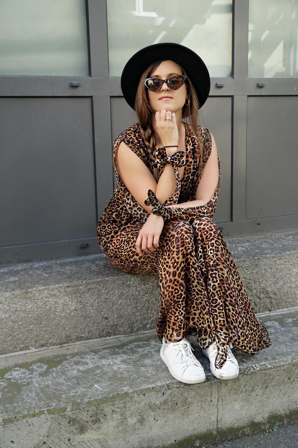 Ein Kleid im Leoparden-Muster mit einer Bauchtasche und weissen Turnschuhen. Für die Casual Variante trägt Andrea vom Mode Blog Strawberries 'n' Champagne dazu ein schwarzer Hut und eine Tat Eye Sonnenbrille.