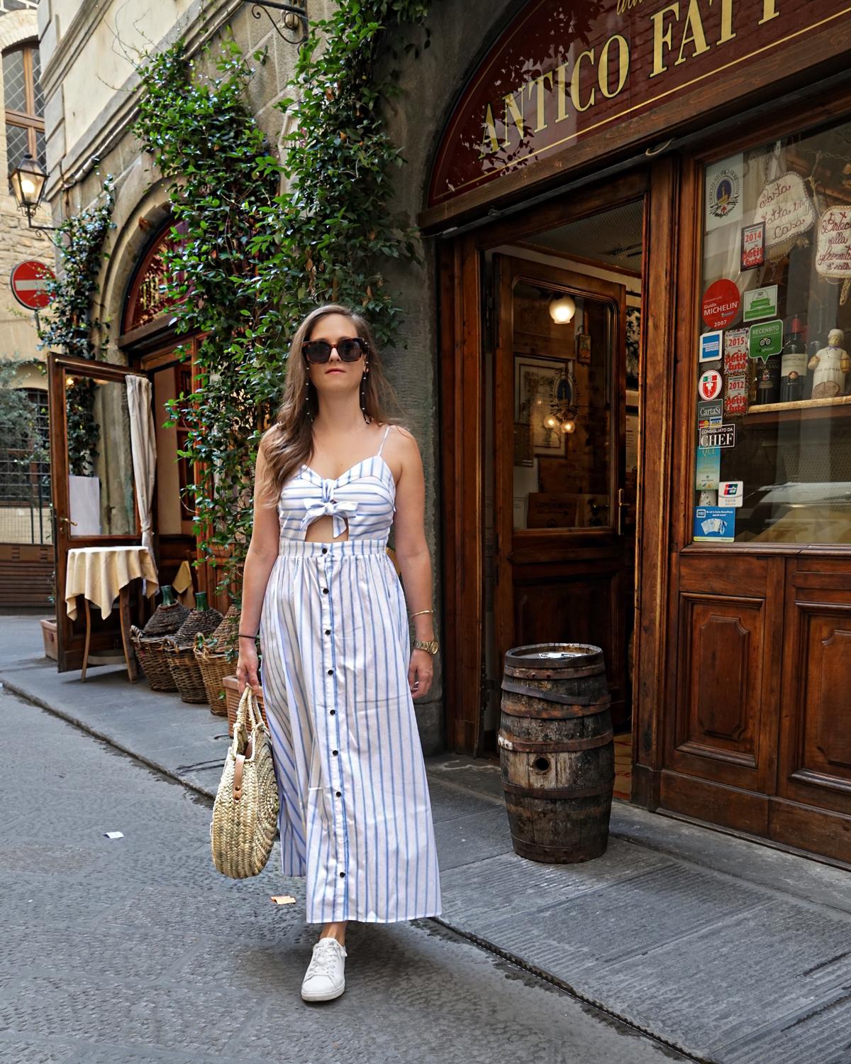 Ein weisses Kleid mit blauen Streifen, dazu eine Strohtasche und weisse Sneakers für eine Städtereise in Florenz, Italien.