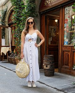 A long white dress with blue stripes, a straw bag and some sneakers for a casual day in Florence.