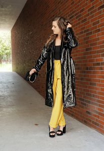 black patent leather coat with yellow pants and high heels.