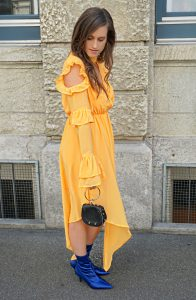Orange long dress with ruffles and cut outs and some blue boots.