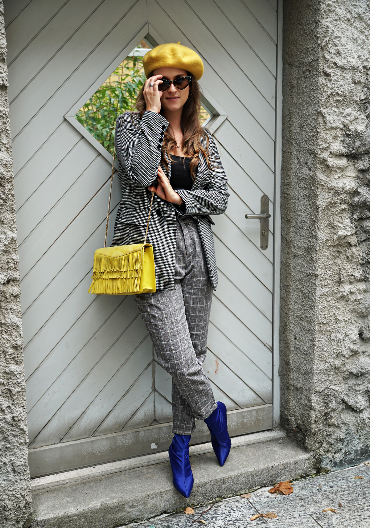 Checked pattern all-over-look with checked pants, checked blazer and a yellow bag with a yellow hat and blue boots.