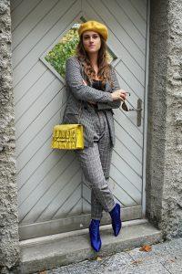 Karomuster im All-Over-Look mit karierter Hose, kariertem Blazer sowie blaue Schuhe mit gelber Tasche und einem gelben Perret.