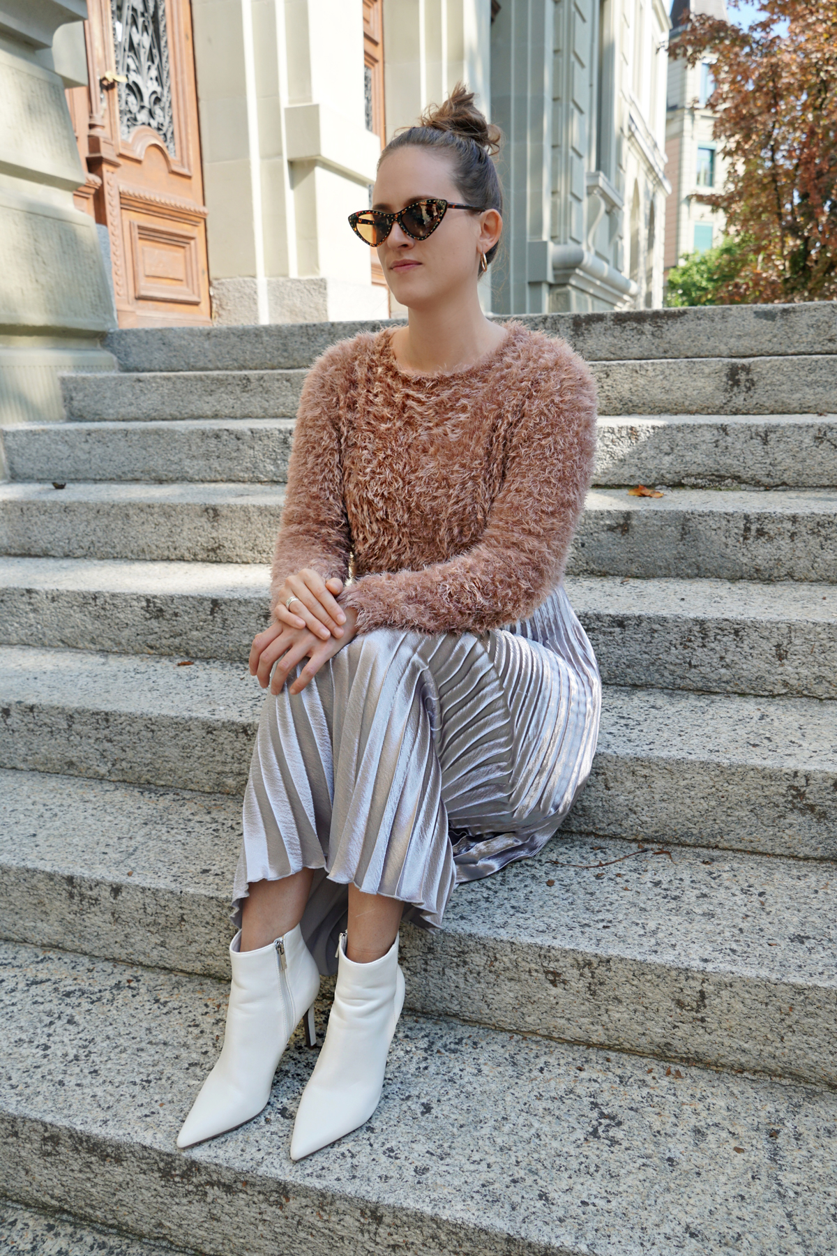 Silver pleated skirt with a sweater and white boots. Fall Trend.