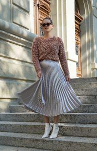 Herbst Trend: Silberner Faltenrock mit einem kurzen Pullover und weissen Boots.