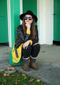 Andrea Steiner, fashion blogger from Strawberries 'n' Champagne based in Switzerland wearing a yellow dress and leather jacket from Zara, jeans from Topshop and shoes from Sorel.