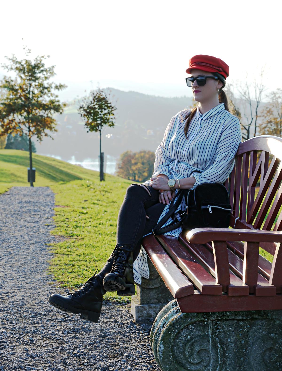 Mein Outfit heute: eine lange weisse Bluse mit schwarzen Boots und schwarzen Hosen, dazu ein roter Boyhat, Rucksack und Sonnenbrille.