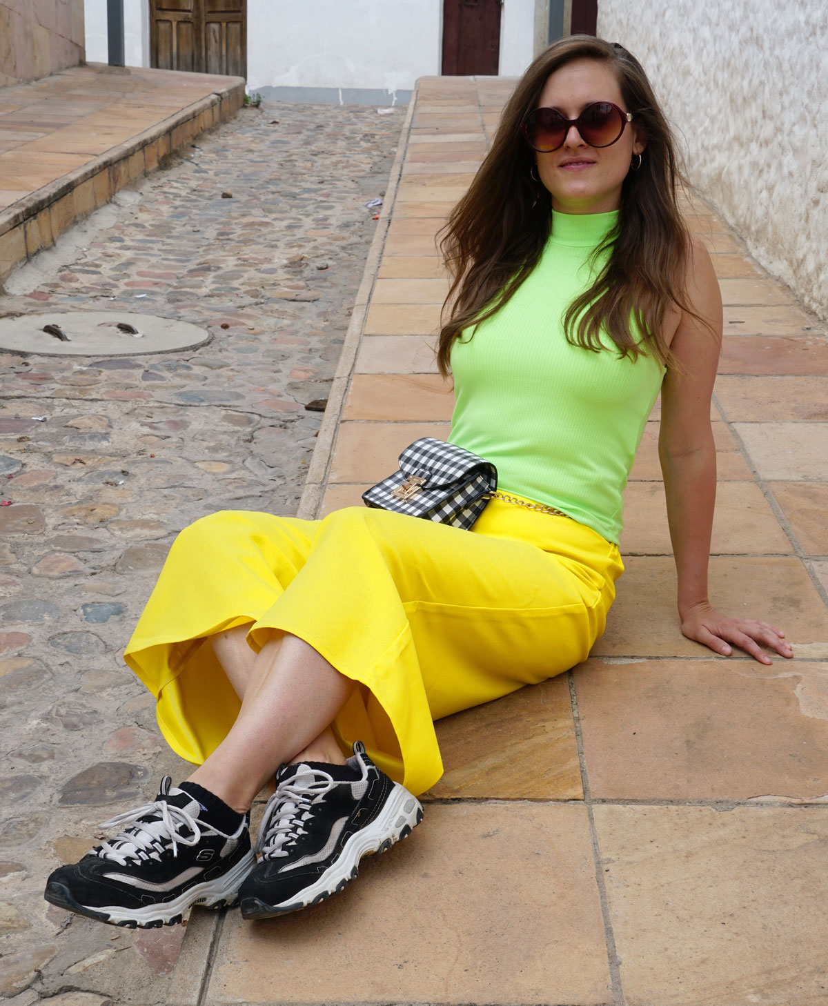 sunshine yellow pants with a neon green shirt, sneakers from Skechers and a bag from Aldo.