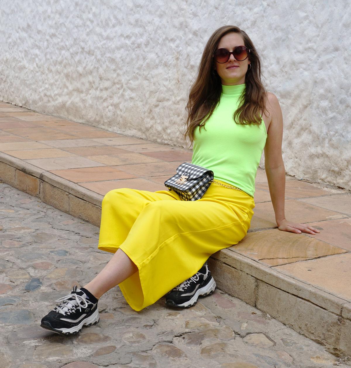 Sonnengelbe Hosen kombiniert mit einem Neongrünen Top. Dazu sneakers von Skechers und einen karierte Tasche von Aldo.