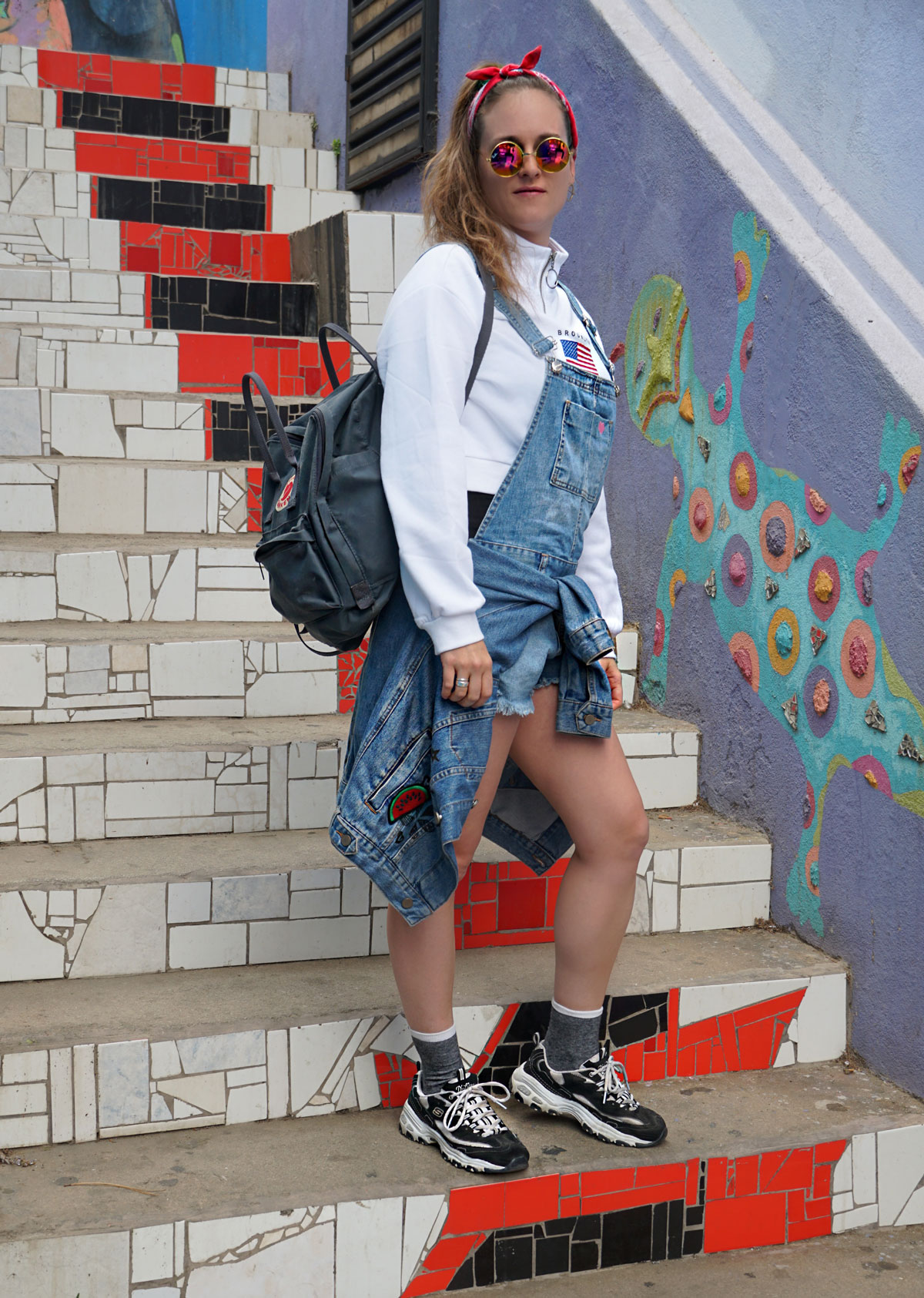 Denim dungarees trend with a sweater and sneakers