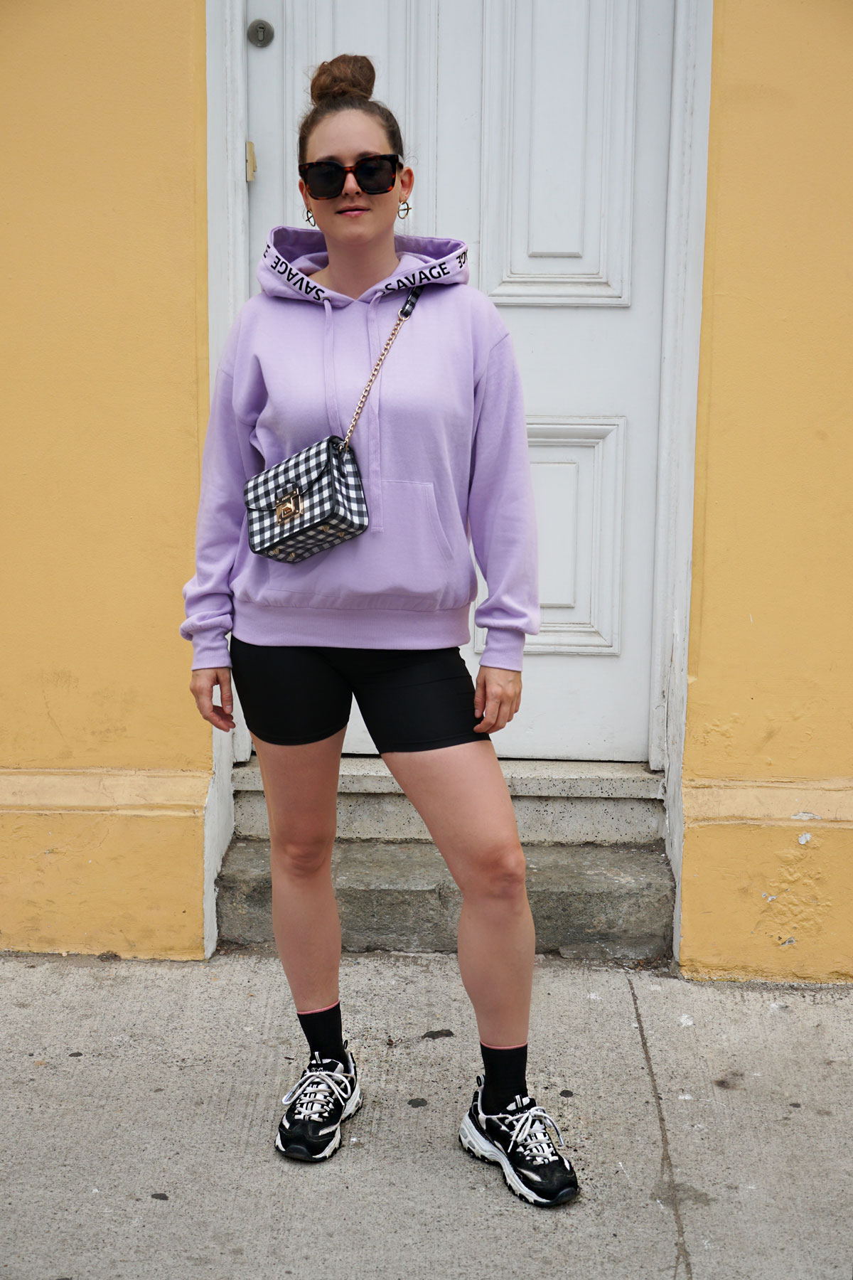 a hoodie the spring color soft lilac with black leggings and sneakers.