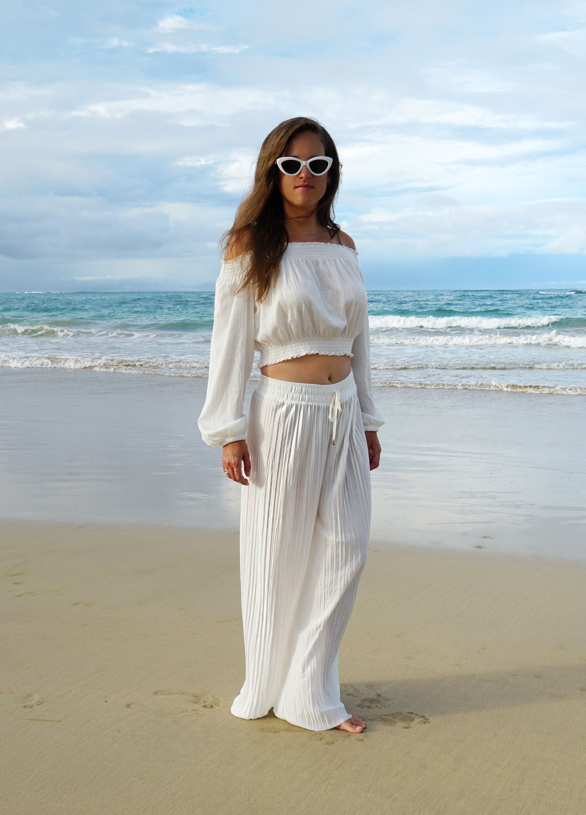 White from head to toe with white pants, and white shoulder off shirt and a white sunglasses.