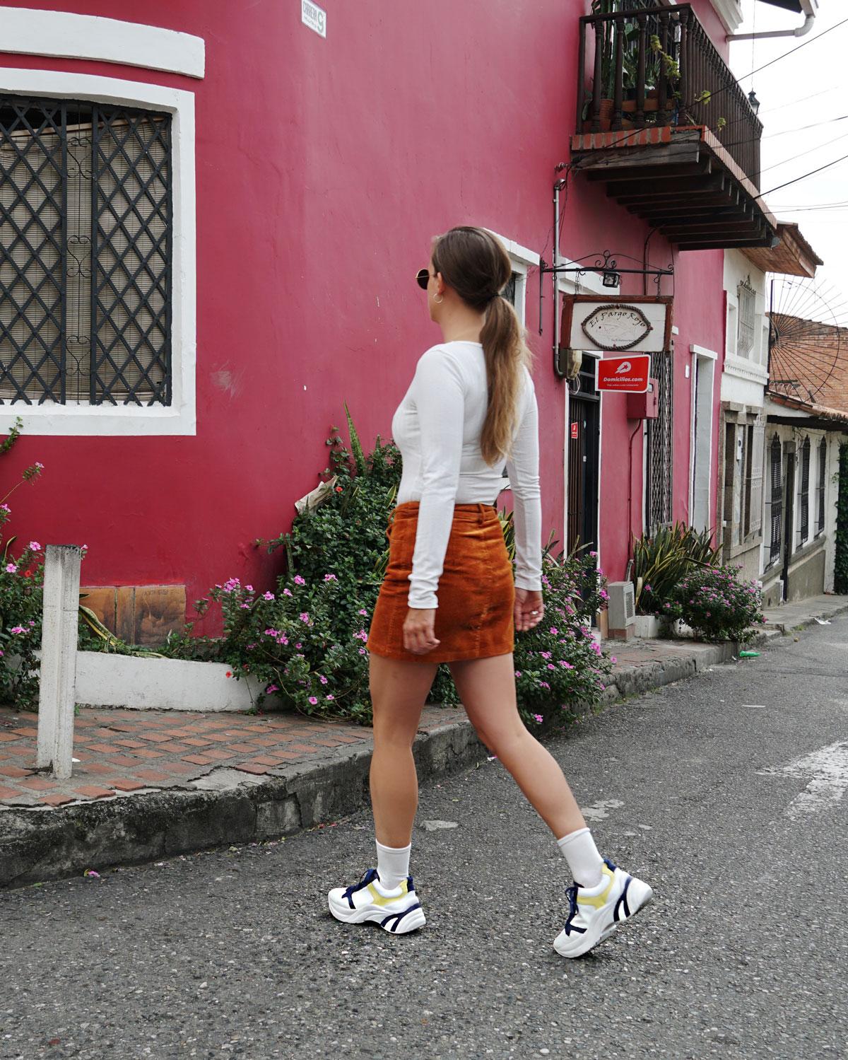 Ein brauner Minirock aus Cord mit weissen Plateau-Sneakers und einem weissen Body.