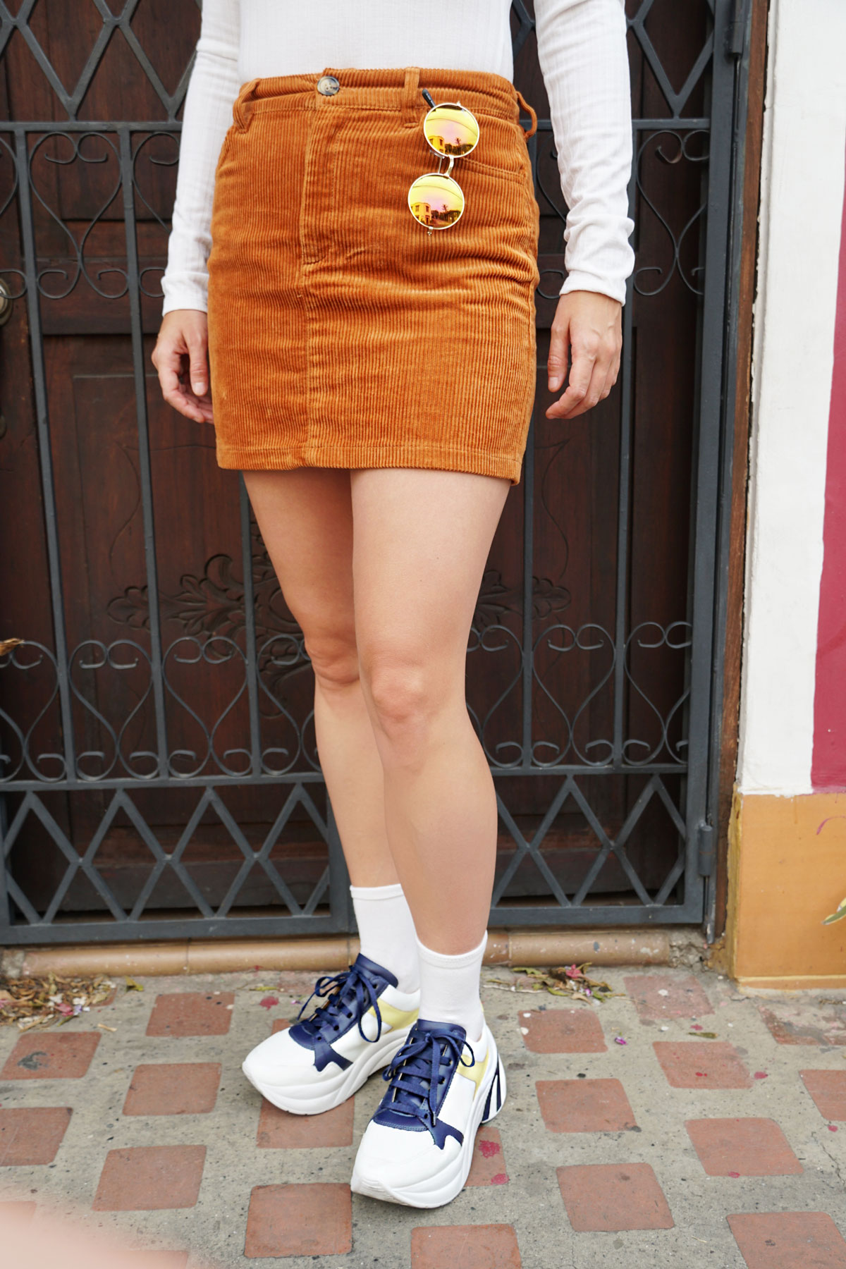 a brown corduroy skirt with a white body suit and plateau sneakers.