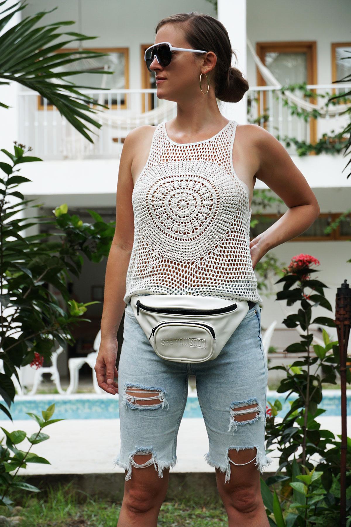Andrea Steiner vom Mode Blog Strawberries 'n' Champagne aus der Schweiz trägt Denim Bermuda Hosen mit einem gestrickten Top, Bauchtasche und Plateau-Sneakers.