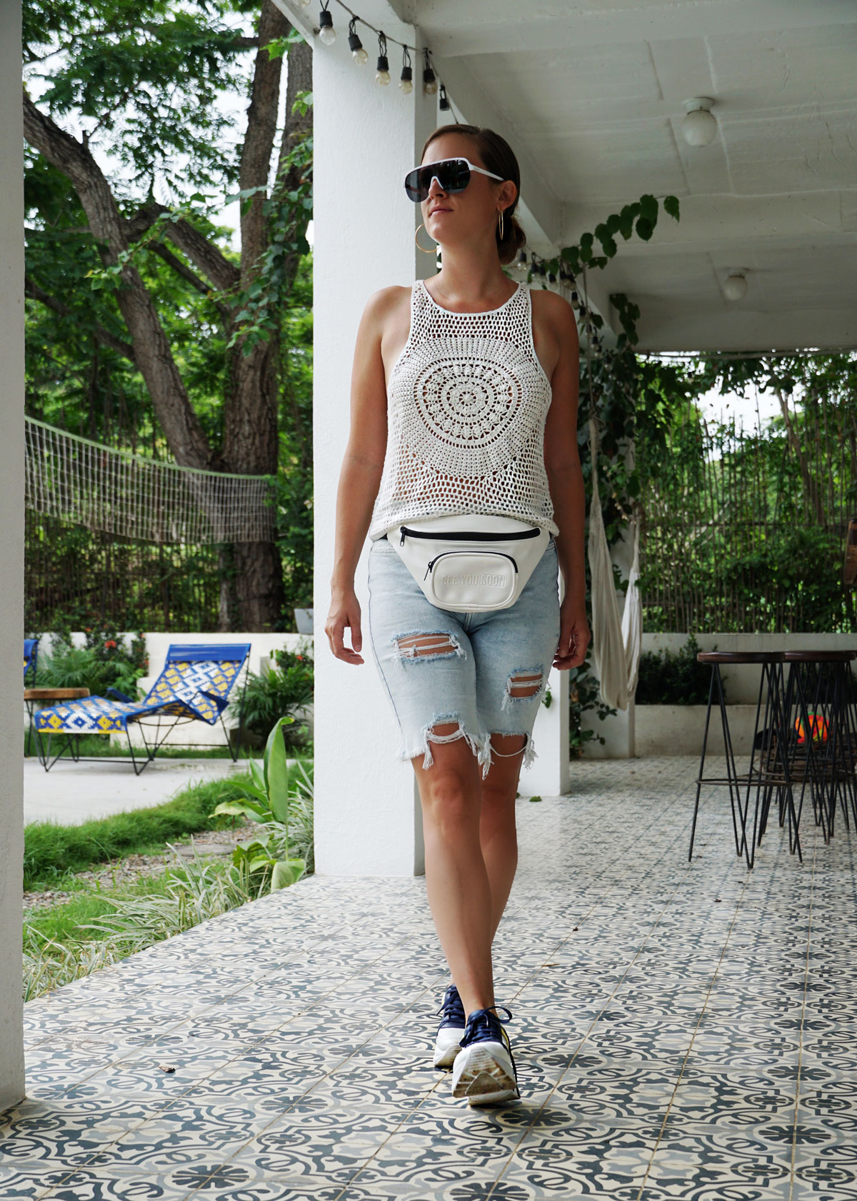 Andrea Steiner from fashion blog Strawberries 'n' Champagne based in Switzerland is wearing denim bermuda shorts with a white shirt, a fanny pack and sneakers.