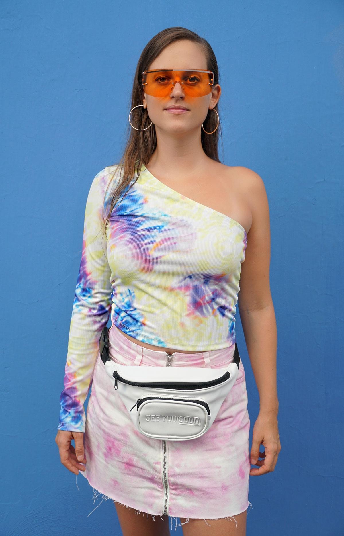 Andrea Steiner vom Mode Blog Strawberries 'n' Champagne trägt ein komplettes Outfit im Batik Muster, dazu eine Bauchtasche, eine orange Sonnenbrille und Sneakers.