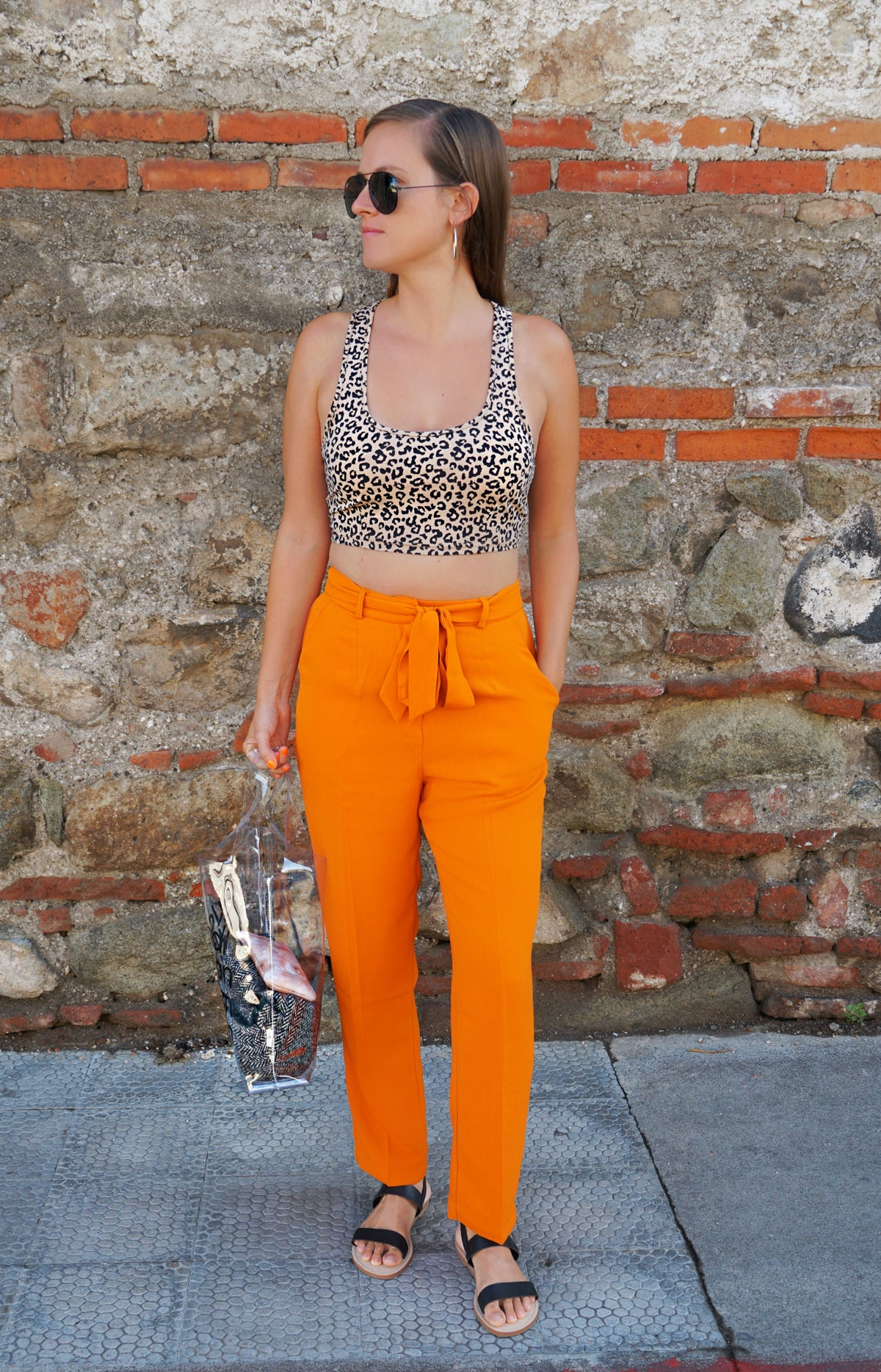 Andrea Steiner, fashion blogger from Strawberries 'n' Champagne based in Switzerland is wearing orange pants with a leopard pattern cropped top, transparent bag and black sandales.