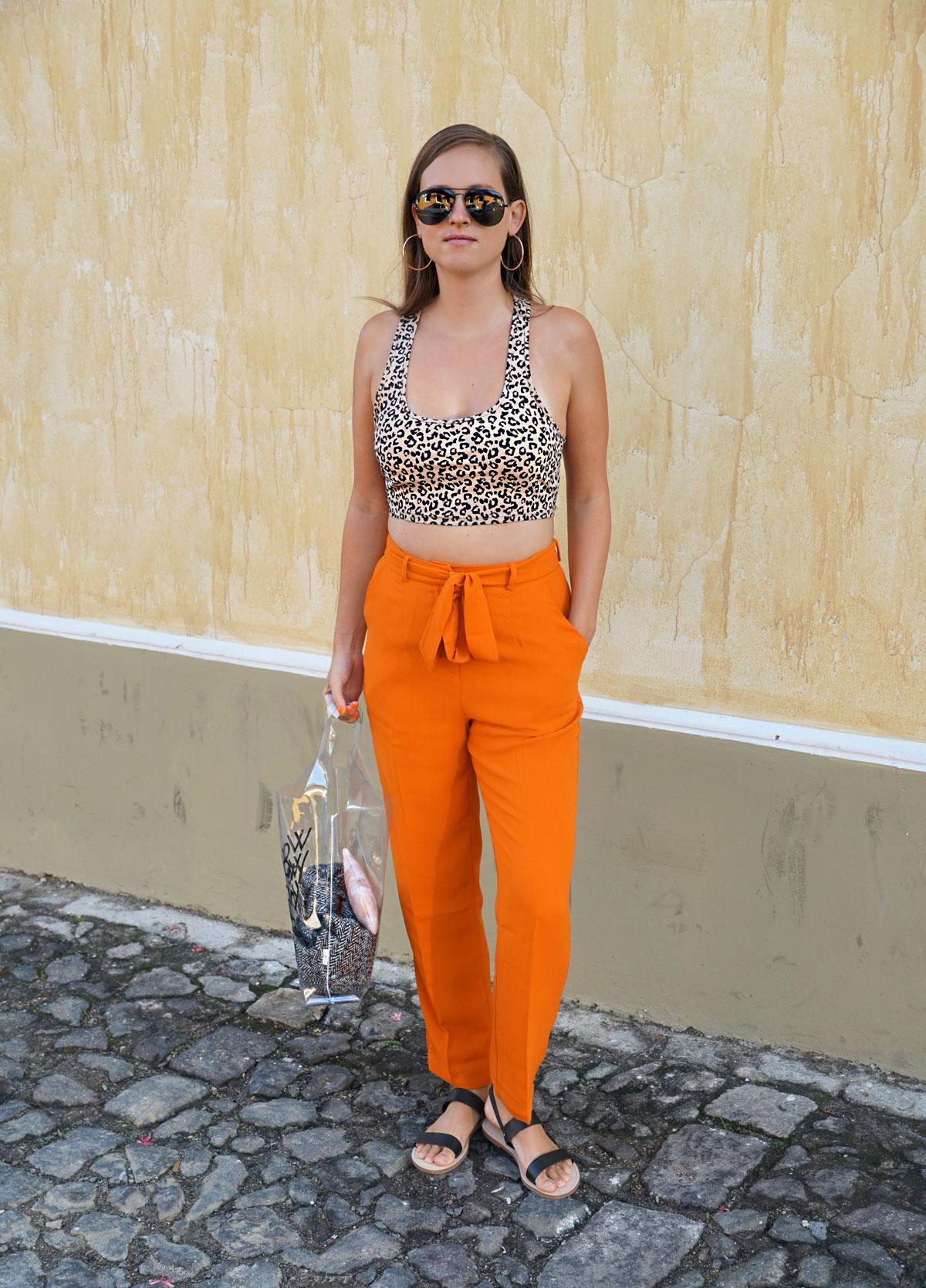 Andrea Steiner vom Mode Blog Strawberries 'n' Champagne aus der Schweiz trägt orange Hosen mit einem kurzen Top im Leopardenmuster mit einer transparenten Tasche und Sandalen.