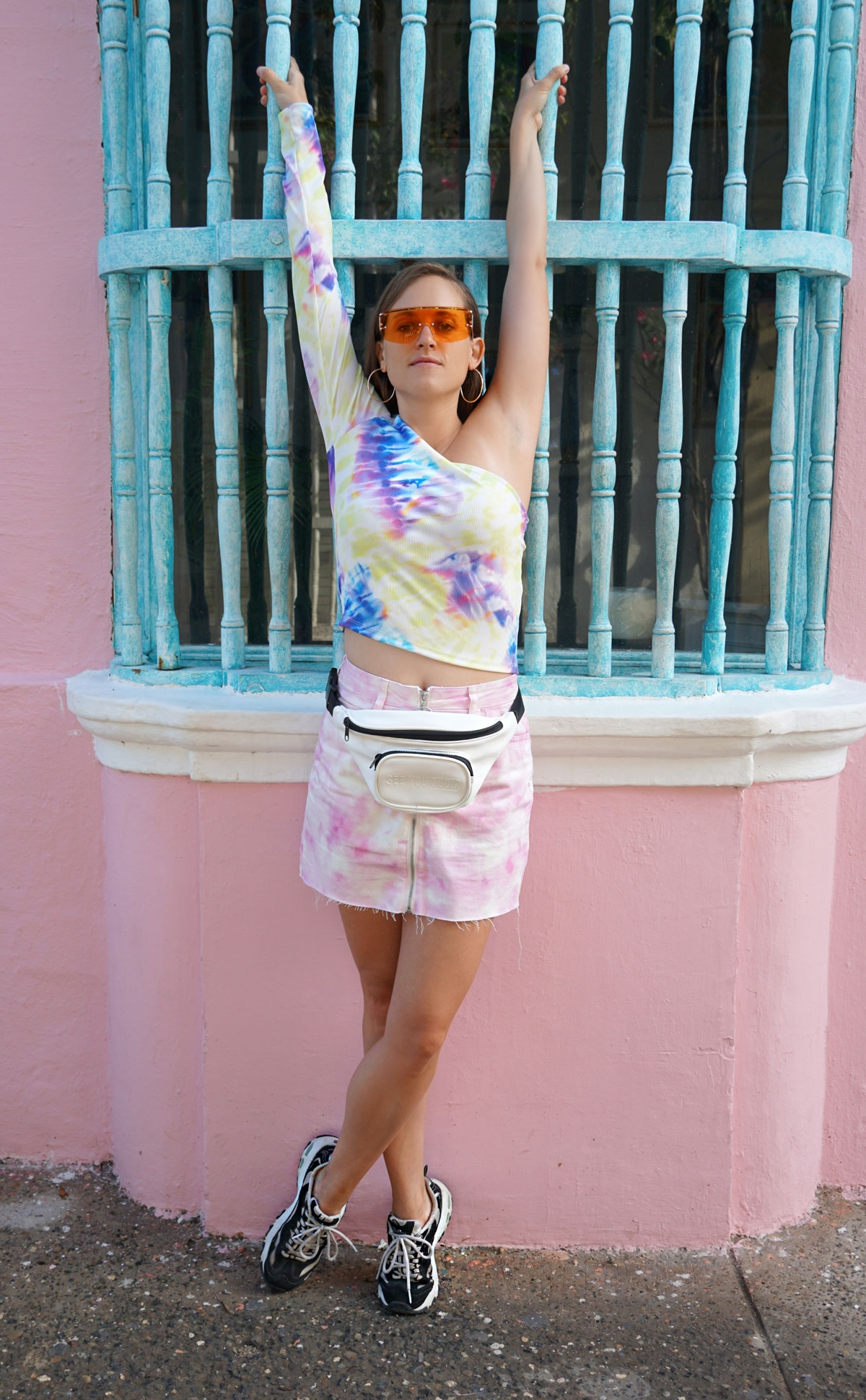 Andrea Steiner from fashion blog Strawberries 'n' Champagne based in Switzerland is wearing a complete tie dye pattern outfit with a white fanny pack, a orange sunglasses and sneakers.